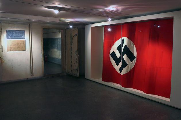 Η ναζιστική σημαία που κυμάτιζε στο κτίριο, και μία πόρτα από το κολαστήριο της Γκεστάπο στην οδό Μέρλιν. Μάριος Βαλασόπουλος