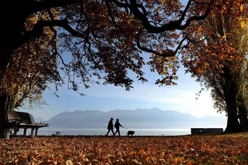 Ζευγάρι απολαμβάνει τον ασυνήθιστα ζεστό για την εποχή καιρό στη λίμνης της Γενεύης, στην Ελβετία.
