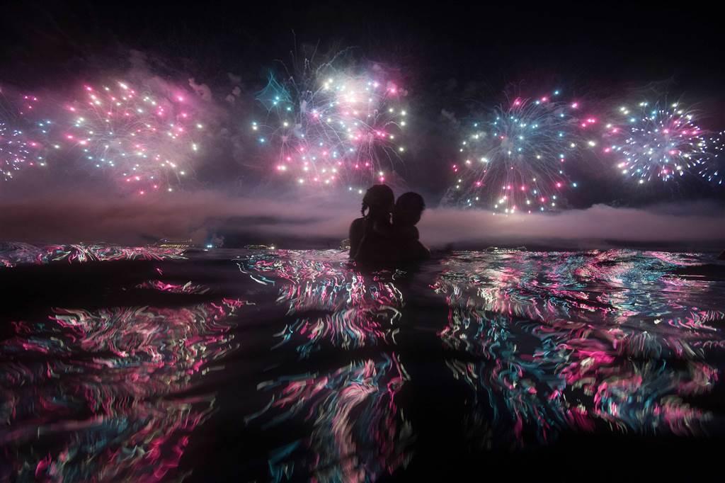 Ένα ζευγάρι την πρωτοχρονιά παρακολουθεί τα πυροτεχνήματα από την παραλία Copacabana στο Ρίο ντε Τζανέιρο. @CHRISTOPHE SIMON / AFP