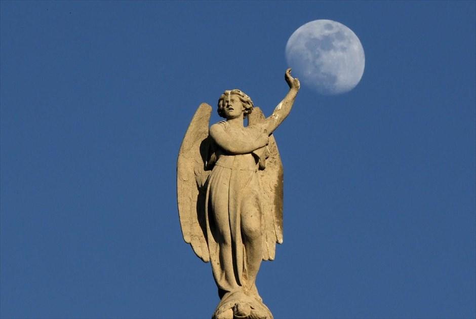 Το φεγγάρι ανατέλλει πίσω από άγαλμα της εκκλησίας Σεν Ζερμέν λ' Οσερουά, στο κέντρο του Παρισιού. @REUTERS / CHRISTIAN HARTMANN