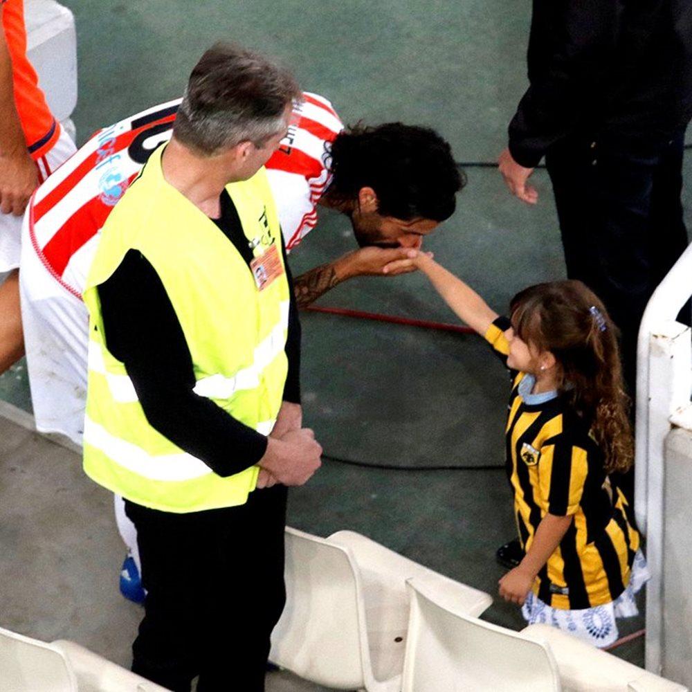 """Αν είχαμε να επιλέξουμε κάτι, μια σκηνή, ένα στιγμιότυπο που θα αποτύπωνε τόσο πιστά αυτό που πρεσβεύει στην ουσία του ο αθλητισμός, τότε η φωτογραφία που προκάλεσε αίσθηση περισσότερο από κάθε τι άλλο φέτος στην Ελλάδα, είναι αυτή με τον Τσόρι που φιλά ιπποτικά το χέρι της μικρής με τα κιτρινόμαυρα μετά το τέλος του τελικού στο ΟΑΚΑ. Ο Ολυμπιακός ηττήθηκε με 2-1 από την ΑΕΚ στον τελικό Κυπέλλου Ελλάδας, όμως ο Αλεχάντρο Ντομίνγκες δεν ξέχασε τους τρόπους του. Ο Αργεντινός άσος των """"ερυθρόλευκων"""" μετά τη λήξη του αγώνα και καθώς κατευθυνόταν προς τη φυσούνα σταμάτησε στο σημείο που βρισκόταν η οικογένεια Μπουονανότε. Εκεί σαν σωστός gentleman φίλησε το χέρι της κόρης του παίκτη της ΑΕΚ, χαρίζοντας στους φωτογράφους μια συγκλονιστική εικόνα. @Βασίλης Μαρούκας,"""