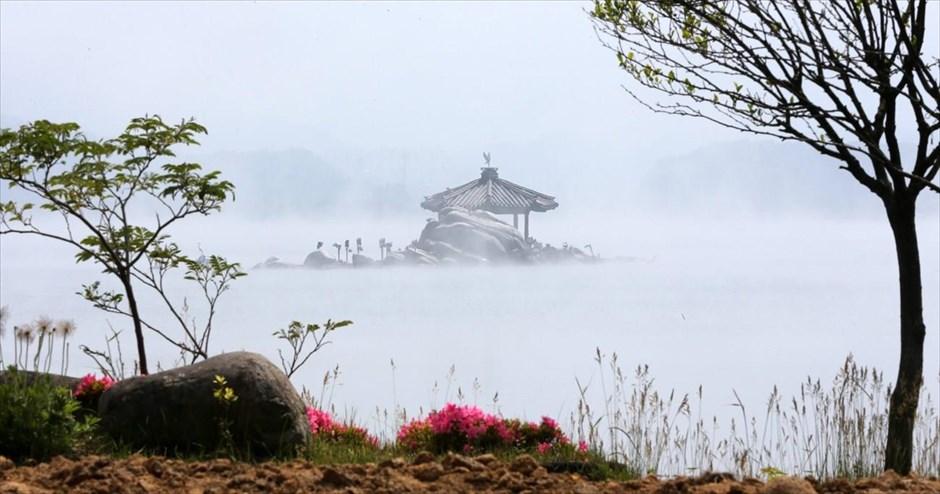 Κιόσκι της λίμνης Γκιονγκπό, στη Νότια Κορέα, ξεπροβάλλει μέσα από την πυκνή ομίχλη που σκεπάζει την περιοχή. @EPA / STRINGER