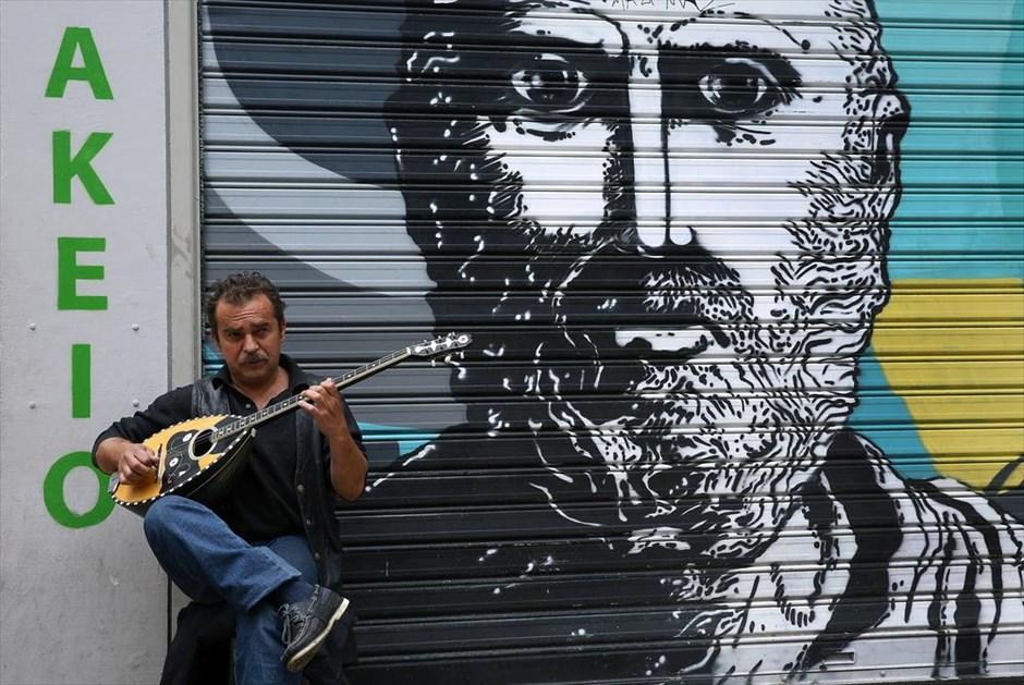 Ένας άντρας παίζει μπουζούκι έξω από ένα κλειστό μαγαζί στου Ψυρρή. @ΑΠΕ-ΜΠΕ / ΣΥΜΕΛΑ ΠΑΝΤΖΑΡΤΖΗ