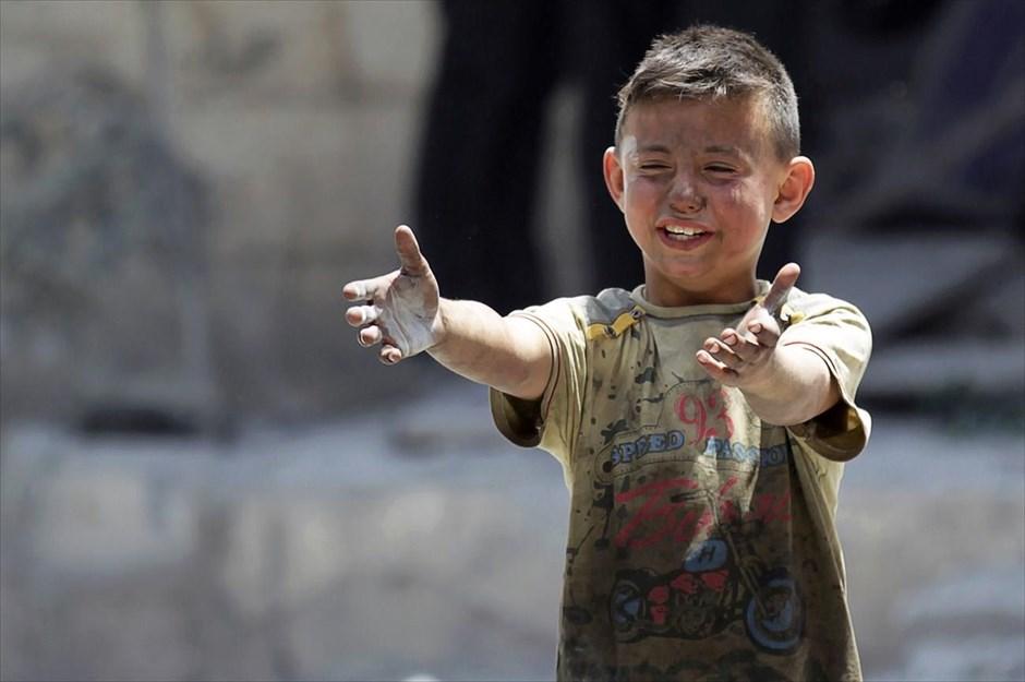 να αγοράκι, του οποίου ο πατέρας σκοτώθηκε στη διάρκεια βομβαρδισμών, κλαίει στο σημείο των επιθέσεων, στην πόλη Μααρέταλ-Νούμαν της επαρχίας Ιντλίμπ της Συρίας. @KHALIL ASHAWI