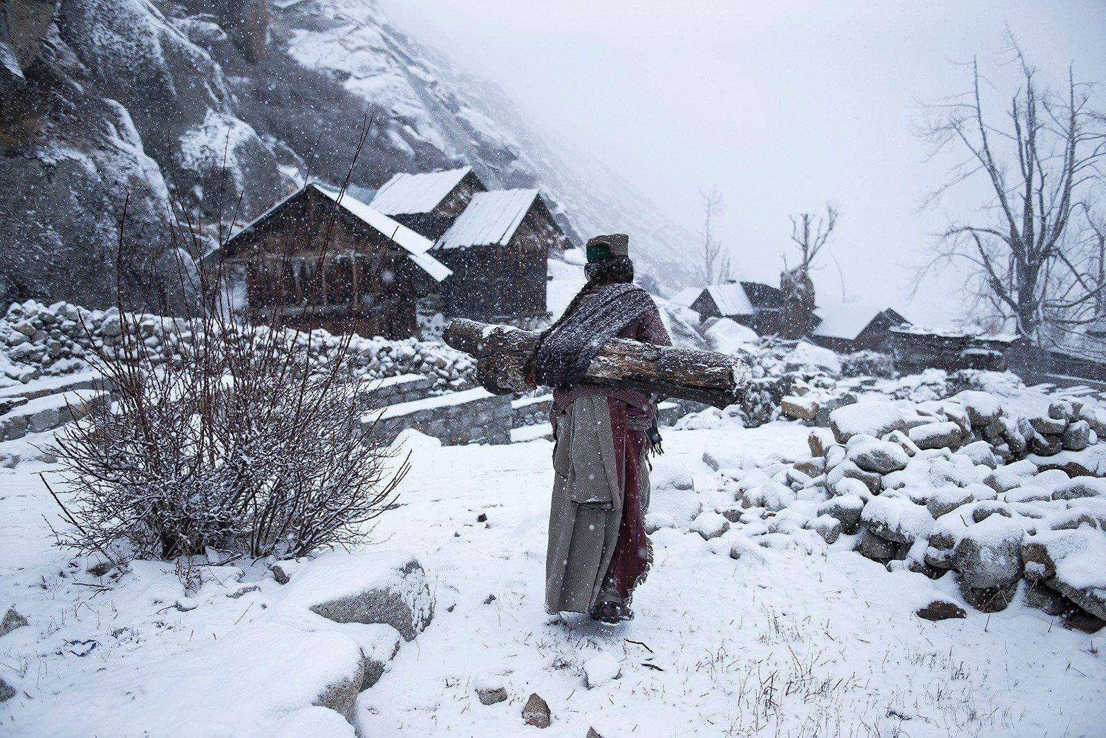 Τρίτη θέση, άνθρωποι: Απομακρυσμένη ζωή στους -21F. Ηλικιωμένη γυναίκα από τη φυλή Kinnaura που ζει σε ένα απομακρυσμένο χωριό της ορεινής Ινδίας κουβαλάει ένα μεγάλο κούτσουρο πίσω στο σπίτι της για να ζεσταθεί. Photograph: Mattia Passarini/National Geographic Travel Photographer of the Year Contest