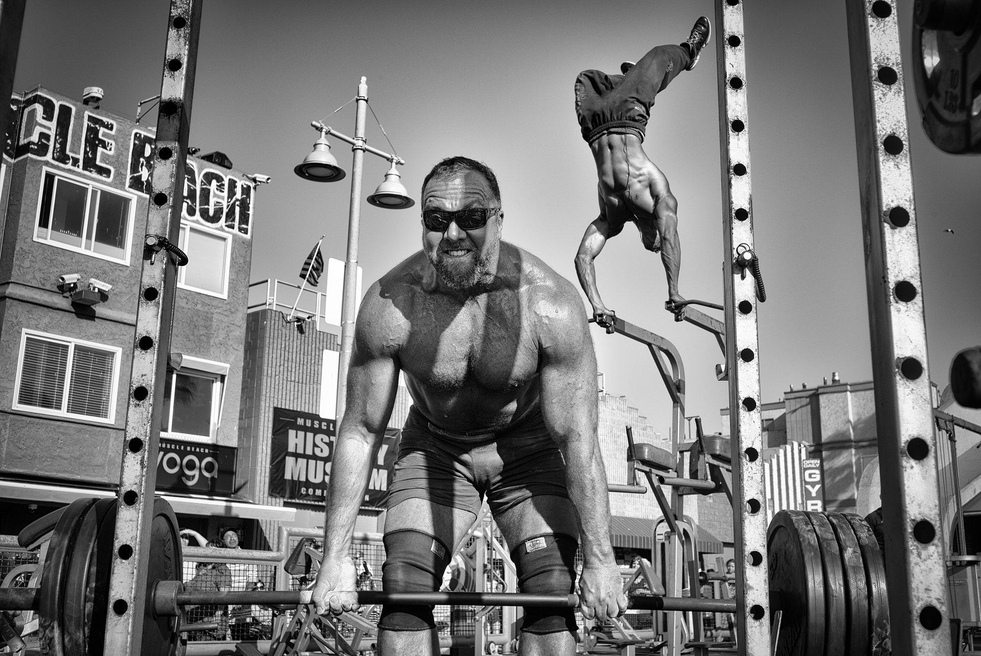 Τιμητική διάκριση, άνθρωποι: Muscle Beach Gym. Ένας αρσιβαρίστας σηκώνει μια μπάρα φορτωμένη με βάρη, ενώ ένας bodybuilder εκτελεί μια εναέρια άσκηση στο γυμναστήριο της Venice Beach στην Καλιφόρνια. Photograph: Dotan Saguy/National Geographic Travel Photographer of the Year Contest