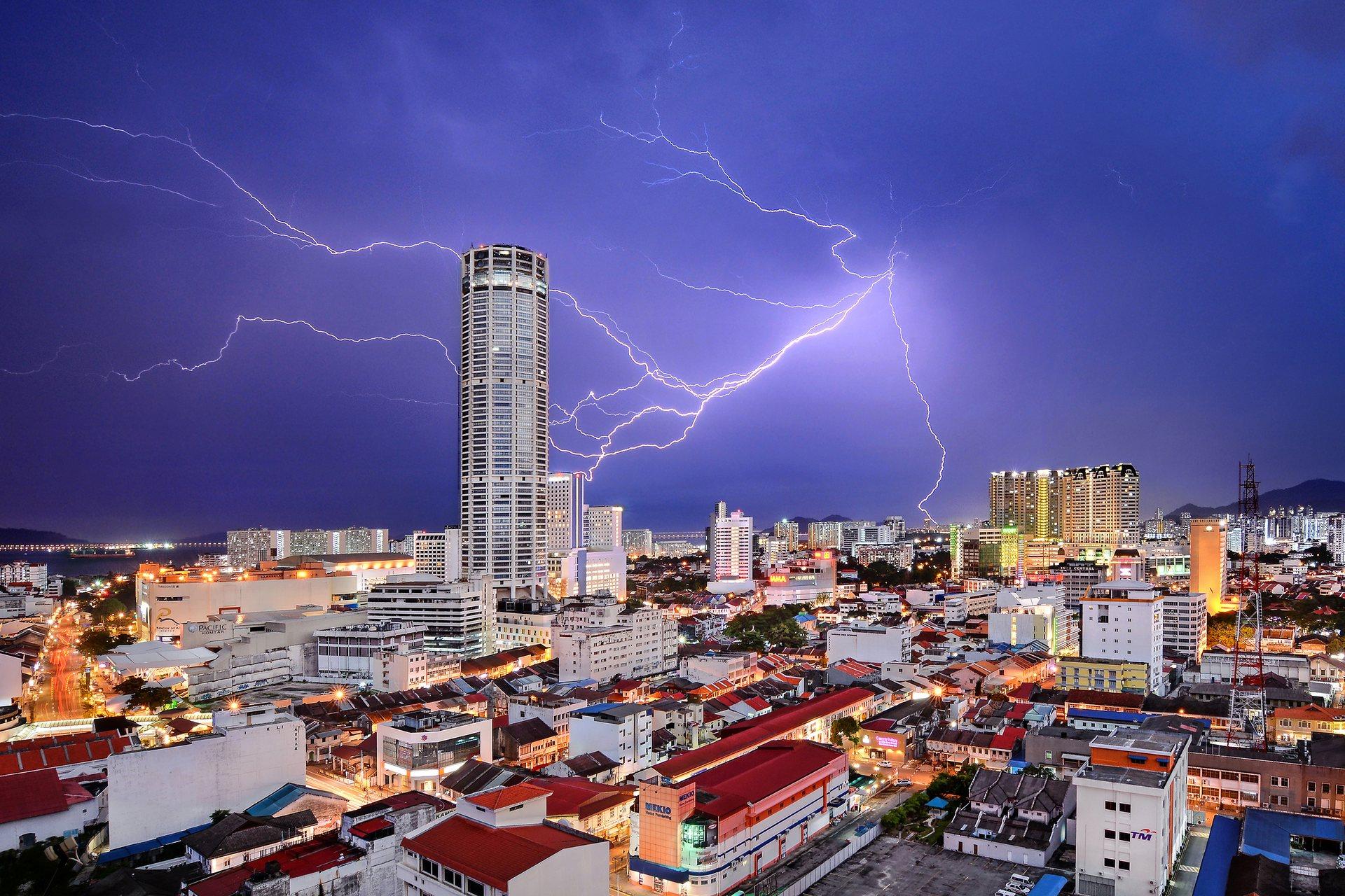 Τρίτη θέση, πόλεις: Celestial Reverie. Κεραυνός μοιάζει να χτυπά τον πύργο Komtar, το πιο χαρακτηριστικό ορόσημο της George Town (πρωτεύουσα της πολιτείας Penang στην Μαλαισία) και σύμβολο της αναγέννησης που γνωρίζει η πόλη τα τελευταία χρόνια, διάσημη για το μοναδικό μείγμα των αρχαίων κτιρίων και των σύγχρονων δομών. Ενώ πολλές από τις παλιές γειτονιές της έχουν παραμεληθεί τη δεκαετία του 1990 και στις αρχές του 2000, το 2008 μια λίστα Παγκόσμιας Κληρονομιάς της UNESCO πυροδότησε μια σημαντική μεταμόρφωση και σήμερα είναι όλα μέρος ενός ζωντανού τουριστικού προορισμού. Photograph: Jeremy Tan/National Geographic Travel Photographer of the Year Contest