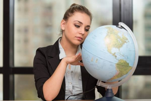 Portrait Of A Woman Sitting By Her Desk And Holding A Globe Model
